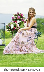 a portrait of a beautiful bridesmaid smiling in the middle of the nature seating next to bouquets of colorful flowers