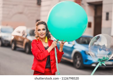 portrait of a beautiful bright girl on a city street lifestyles with green balloons smiling and posing in a red suit