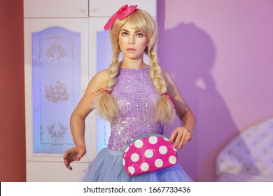 Portrait of a beautiful and bright woman doll. She is holding a makeup bag.