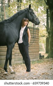 Portrait of a beautiful brown hair woman dressed in black  and black horse outdoor. Day shot