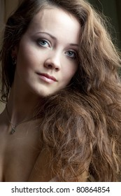 portrait of a beautiful brown-haired with soft wavy hair on a black background