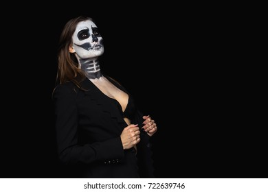 portrait beautiful of brown-haired woman with Halloween skull make up in a stylish black jacket and bra over black background.
