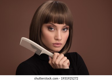 Portrait of a beautiful brown-haired woman holding comb in her hand. Brown background.
