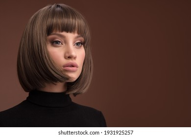 Portrait of a beautiful brown-haired woman with a short haircut on a brown background
