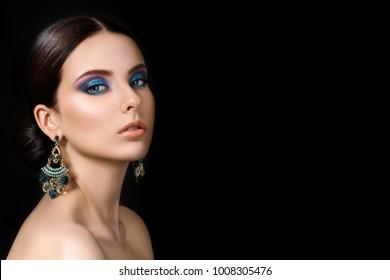Portrait of beautiful brunet woman with blue earrings posing over black background. Modern fashion make up. Studio shot