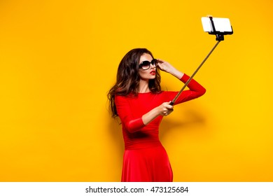 Portrait of beautiful brunette in awesome dress and red lips wearing sunglasses while making selfie with stick. Isolated