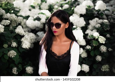 Portrait of a beautiful brunette. Background of flowers