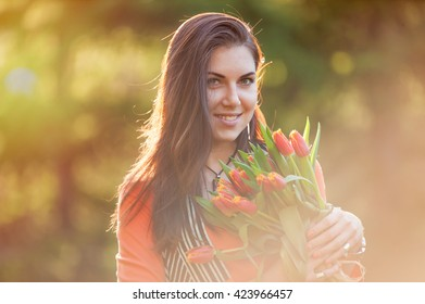 Portrait of a beautiful brunette with a bouquet of tulips in her hands.
