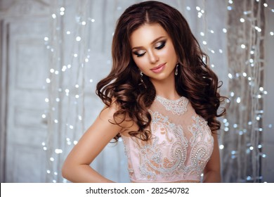 Portrait of Beautiful Brunette Bride in Lights. Fashion Dress and MakeUp