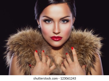 Portrait of a beautiful brunette with classic make up and red lips, holding her hands on fur