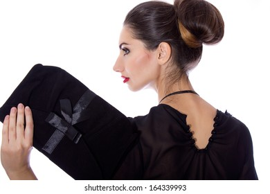 Portrait of a beautiful brunette in designer clothes with red lipstick in the studio