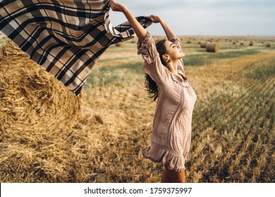 Portrait of a beautiful brunette in a dress and with a warm plaid. Woman enjoying a walk in a wheat field with hay bales.