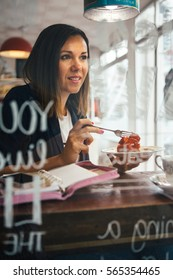 Portrait of beautiful brunette eating strawberry pie in cafe with organizer on table