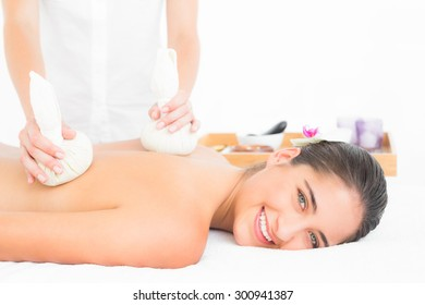 Portrait of beautiful brunette enjoying a herbal compress massage at the health spa