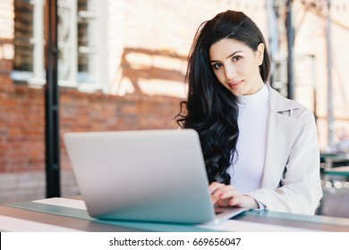 Portrait of beautiful brunette female freelancer typing a message via email using laptop while sitting on terrace looking at camera with confident look. Young lady working with computer outdoors
