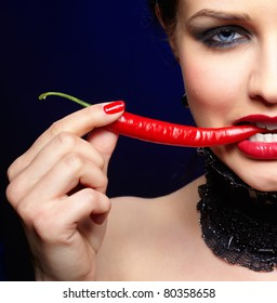 portrait of beautiful brunette girl biting spicy hot red cayenne chili pepper