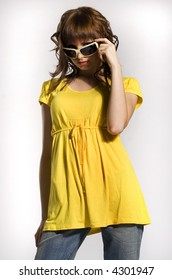 a portrait of beautiful brunette girl dressed in yellow clothes on white background
