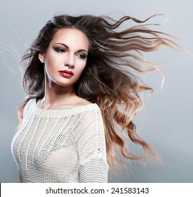 Portrait of a beautiful brunette girl with fluttering hair with wind. Windy hair