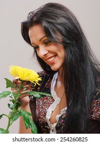 Portrait of the beautiful brunette girl with healthy long hair, holding in hand yellow flower.