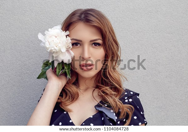 Portrait of a Beautiful brunette girl with nude make up and fresh skin. Attractive female holding peony flower near face. Skin care concept, beauty spa, bio product. Grey background