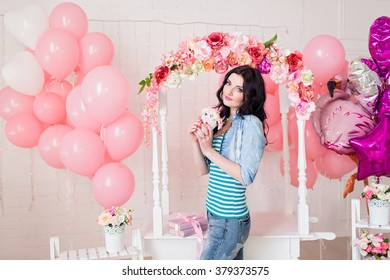 Portrait of beautiful brunette girl on background of flowers and pink balloons