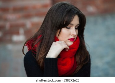 Portrait of beautiful brunette girl with red scarf outside. attractive young caucasian woman in warm colorful clothing
