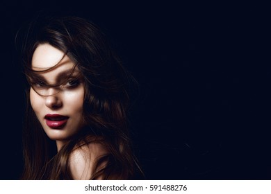 Portrait of a beautiful brunette girl in the studio on a black background