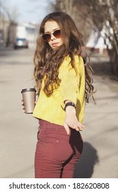 Portrait of beautiful brunette girl with walking down the street. Keeping takeaway drink in her hand. Wearing sunglasses. Urban city scene. Warm sunny weather. Outdoors