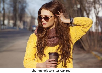 Portrait of beautiful brunette girl walking down the street. Keeping takeaway drink in one hand, other next to her head. Smiling. Urban city scene. Warm sunny weather. Outdoors