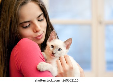 Portrait of a beautiful brunette holding a cute kitten.