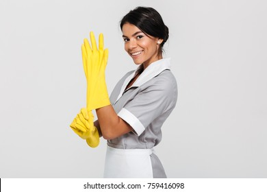 Portrait of beautiful brunette housekeeper in uniform wearing yellow rubber gloves while smiling and looking at camera, isolated on white backgrund