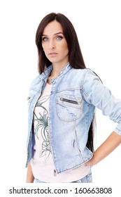 Portrait of a beautiful brunette in jeans jacket who is posing over a white background