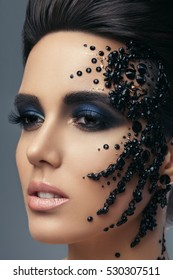 Portrait of a beautiful brunette with makeup beauty and adornment on the face in the form of black stones
