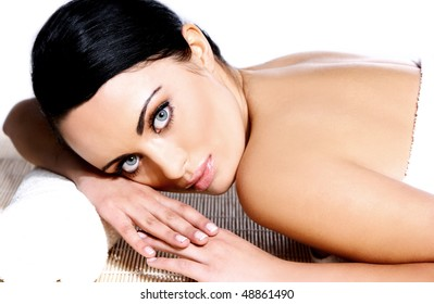 Portrait of a beautiful brunette relaxing in spa on a white background