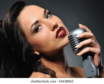 Portrait of a beautiful brunette with a retro microphone