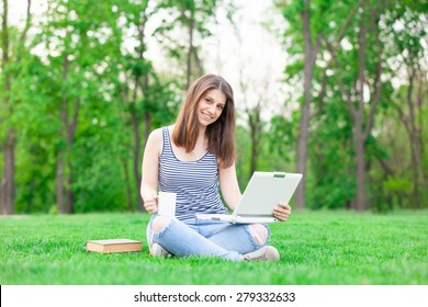 portrait of a beautiful brunette student girl with laptop computer and cup on the green grass in the park in spring time.