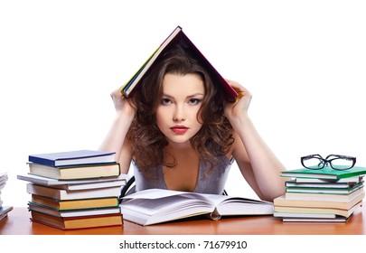 portrait of beautiful brunette student girl sitting among the books