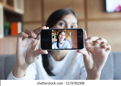 Portrait of a beautiful brunette taking a selfie with her smart phone in the cafe