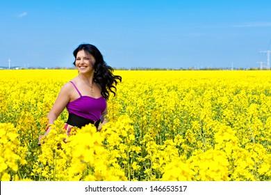 Portrait of a beautiful brunette in violet dress in oilseed rape field