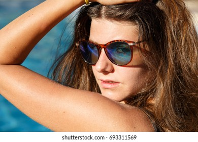 Portrait of beautiful brunette wearing sunglasses and posing in pool looking at camera.