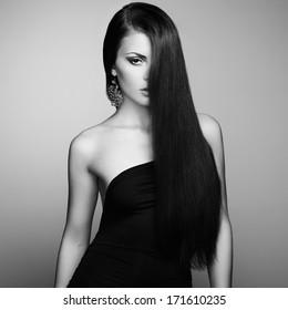 Portrait of beautiful brunette woman in black dress. Fashion photo