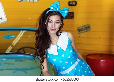 Portrait of a beautiful brunette woman in a blue dress in polka dots with a bow on her head standing near a blue car