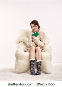 Portrait of beautiful brunette woman with book in hands. Female is dressed in white cashmere sweater and woolen socks. Girl is sitting on white fur arm-chair  staying on furry carpet
