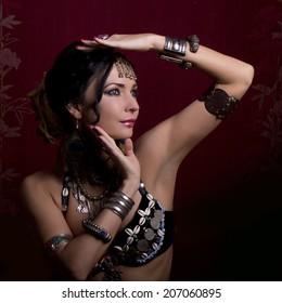 portrait of a beautiful brunette woman dancing tribal