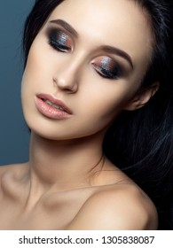 Portrait of beautiful brunette woman with evening makeup. Shiny multicolor smokey eyes. Luxury skincare and modern fashion makeup concept. Studio shot.