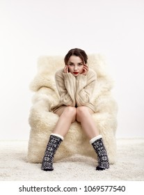 Portrait of beautiful brunette woman. Female is dressed in white cashmere sweater and woolen socks. Girl is sitting on white fur arm-chair  staying on furry carpet