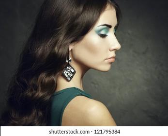 Portrait of beautiful brunette woman in green dress. Fashion photo