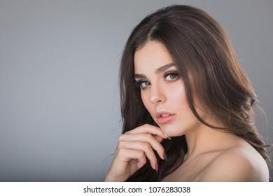 Portrait of beautiful brunette woman holding hand on chin
