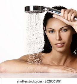 Portrait of a  beautiful brunette woman holds shower in hands  with falling water