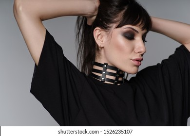 Portrait of beautiful brunette woman with leather black choker